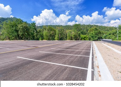 Empty parking lot with forest and beautiful blue sky.