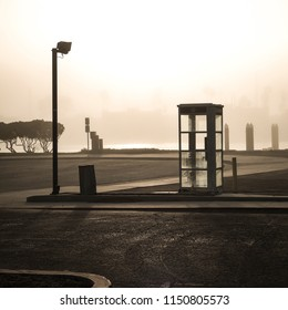 An empty parking lot with a street lamp, phone booth and trash can on a foggy morning with water and shadows in the background