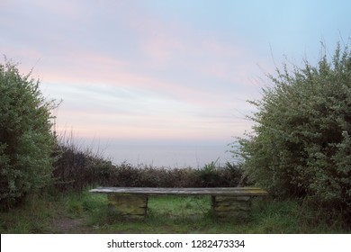 Empty peaceful bench in front of the sea during sunset in France.