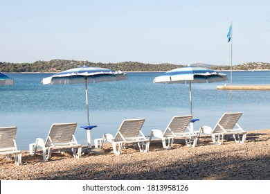 Empty pebble beach in Vodice, Croatia with parasols and chairs