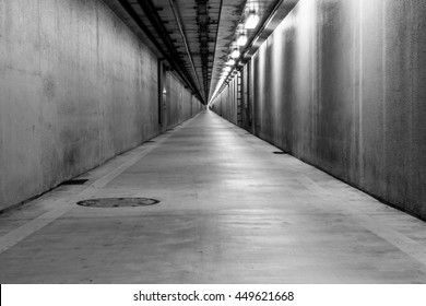 Empty pedestrian and cyclist tunnel linking between land and artificial island in an industrial district of Kawasaki, Japan. Black and white.