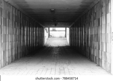 an empty pedestrian passage tunnel with light at the end