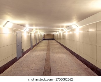 empty pedestrian tunnel underpass with granite trowel on the floor, empty without people. Underpass with light. Beige color.