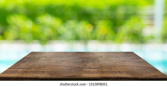 Empty perspective hard wood table and blurred hedge and swimming pool sunlight background. product display template.Business presentation