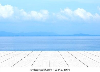 Empty perspective white wood  over blur blue sea and sky in summer background, product display montage background, banner