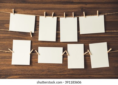 empty photo frames hanging with clothespins on wooden background