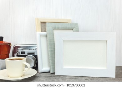 empty photo frames, retro camera, red coffee pot and cup on wooden desk