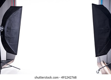 Empty photo studio with lighting equipment and white paper background ready for photoshoot