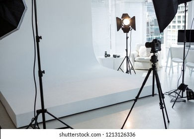 Empty photo studio with tripod, lighting equipment and digital camera