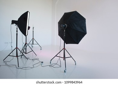 An empty photo Studio with  white cyclorama. Monoblocks with flashes using softboxes of different shapes
