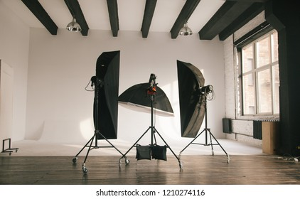 An empty photo Studio with white cyclorama. Monoblocks with flashes using softboxes of different shapes. photographic studio space with white cyclorama and natural light