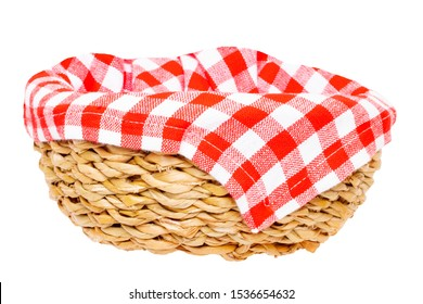 Empty picnic basket. Close-up of a empty straw basket therein a red checkered napkin isolated on a white background. For your food and product display montage. Macro.