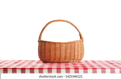 Empty picnic basket on checkered tablecloth against white background