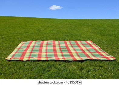 An empty picnic blanket on green grass under blue sky with one cloud. Family holiday concept. No people. Copy space