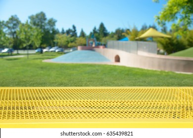 Empty picnic table with blurred playground on background