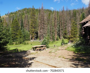 An empty picnic table in the Rocky Mountains National Park in Colorado.  Nearby is a log cabin.  The table is in a clearing with the mountains in the background.