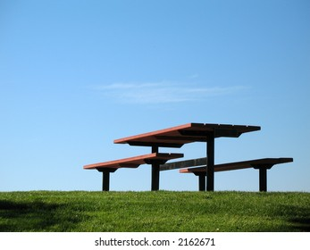 An empty picnic table sits on the green grass and blue sky background