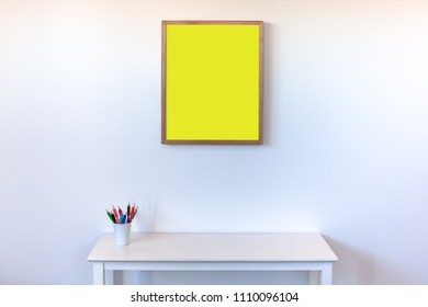 Empty picture frame hanging above white side table with colorful pencils in cup against white wall with copy space