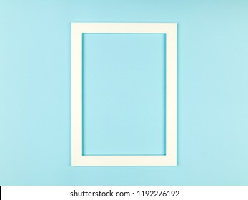 Empty picture frame on textured pastel colored background. Abstract minimalist composition