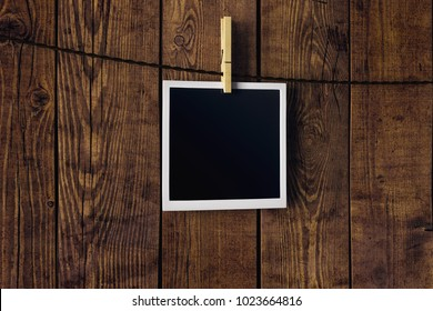 Empty picture hanging on wooden wall background. Photography and art concept. Mock up, 3D Rendering