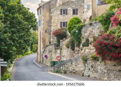 Empty picturesque road along the stone wall and old historical houses in Lacoste, Provence, France.
