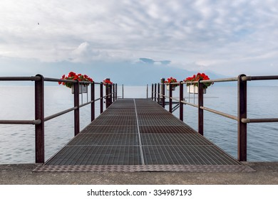 Empty pier flowers decorated on the Geneva lake with view on the French Alps and covered sky.