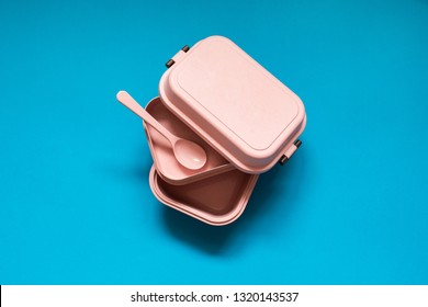 Empty pink bento lunch box with spoon on blue background