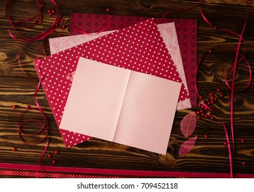 Empty pink greeting card with craft paper and supplies on wooden background.
