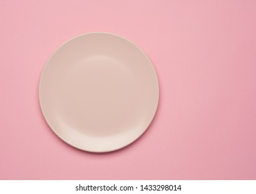 Empty pink plate on the pastel pink background. Flat lay, top view