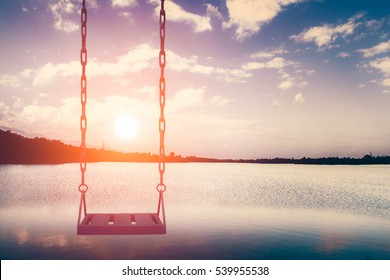 Empty pink swing with blue sea and sky at sunset time background,feel sad or lonely concept
