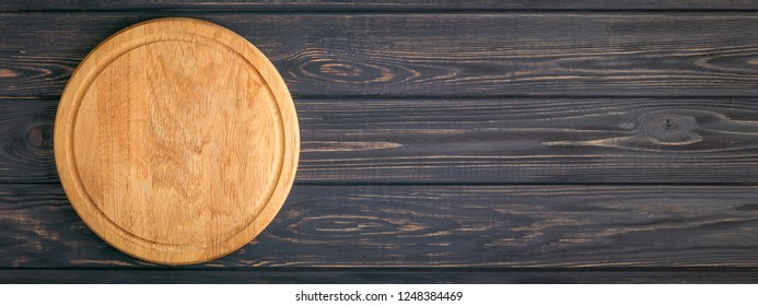 Empty pizza board on dark wooden table. Top view, banner for website.