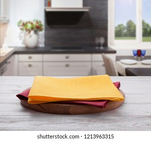 Empty pizza board with tablecloth on the table and kitchen blurred background. Top view mock up. Selective focus.