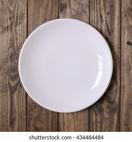 Empty, plain dinner dish on a rustic wooden table top background