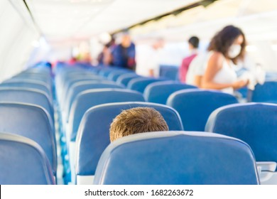 Empty plane interior with few people and stewardess during coronavirus pandemia