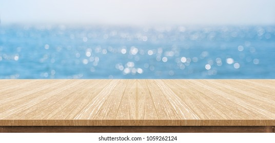 Empty plank wood table top with blur blue sky and sea boekh background,Mock up template for display or montage of product or content use as banner in social media ads.