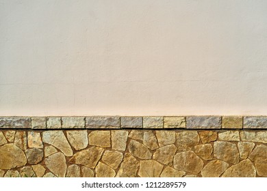 the empty plastered wall with the stone textured plinth for a background or for wallpaper