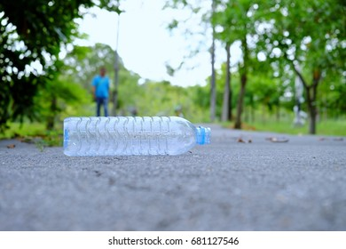 an empty of plastic drinking water bottle littering on the ground floor at the green park with the blur view background