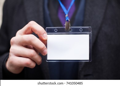 An empty plastic identification card in the hand of a man on the background of a jacket and a blue suit. Layout for text or design. Mock up.