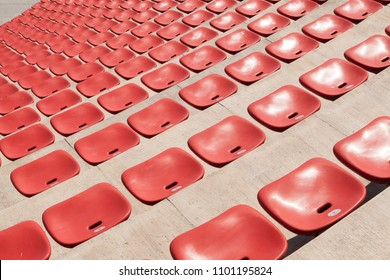 empty plastic red seats on football stadium or amphitheater