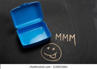 Empty plastic school lunch box on a blackboard with chalk drawings, tongue out smiley face