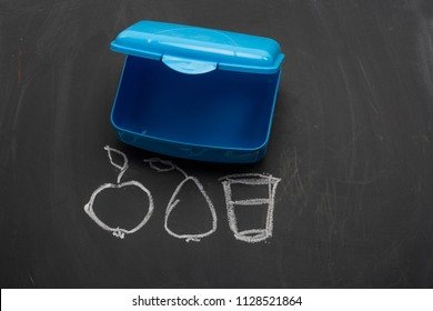 Empty plastic school lunch box on a blackboard with chalk drawings, apple, pear and glass of water