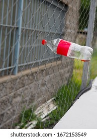 An empty plastic soda bottle stuck in a chain link fence.