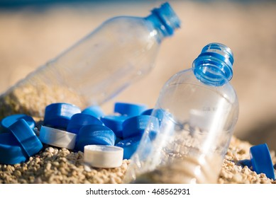 Empty plastic waste bottles on sandy beach with caps