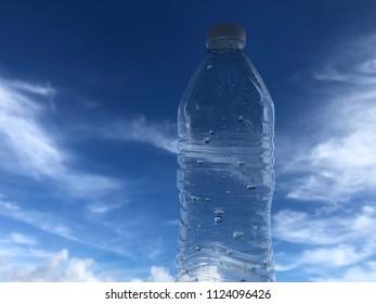 Empty plastic water bottle blue sky cloud background