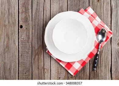 Empty plate, bowl and spoonon wooden table. Top view with copy space