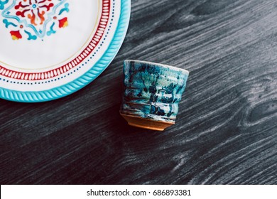 Empty plate and ceramic handmade cup over gray wooden table background. Handmade blue ceramic dishware. View of above with copy space. Homeware concept.