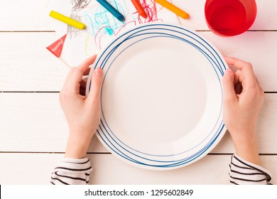 Empty plate in child's hands on white planked wooden background with colorful decorations. Table setting for kids - captured from above (top view, flat lay). Layout with free text (copy) space.