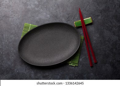Empty plate and chopsticks over black textured table. Japanese food template. Top view with copy space. Flat lay