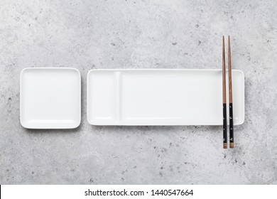 Empty plate and chopsticks over stone table. Japanese food template. Top view with copy space. Flat lay