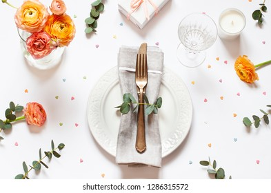 Empty plate concept flat lay with floral decorations on the white backdround. Top view Valentines day, Mothers day or Easter card.